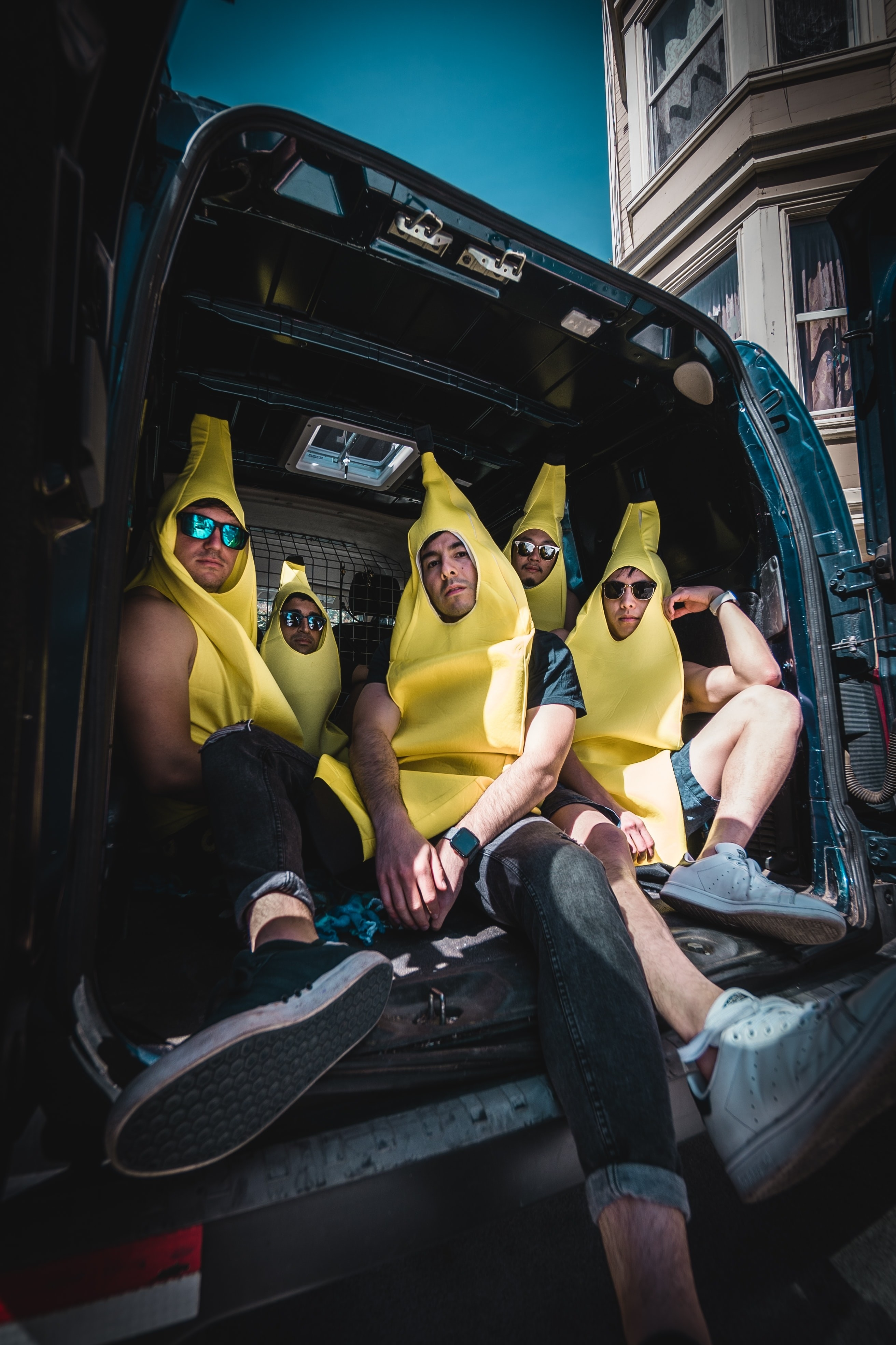 Five white men dressed in banana suits are sitting in the back of a van