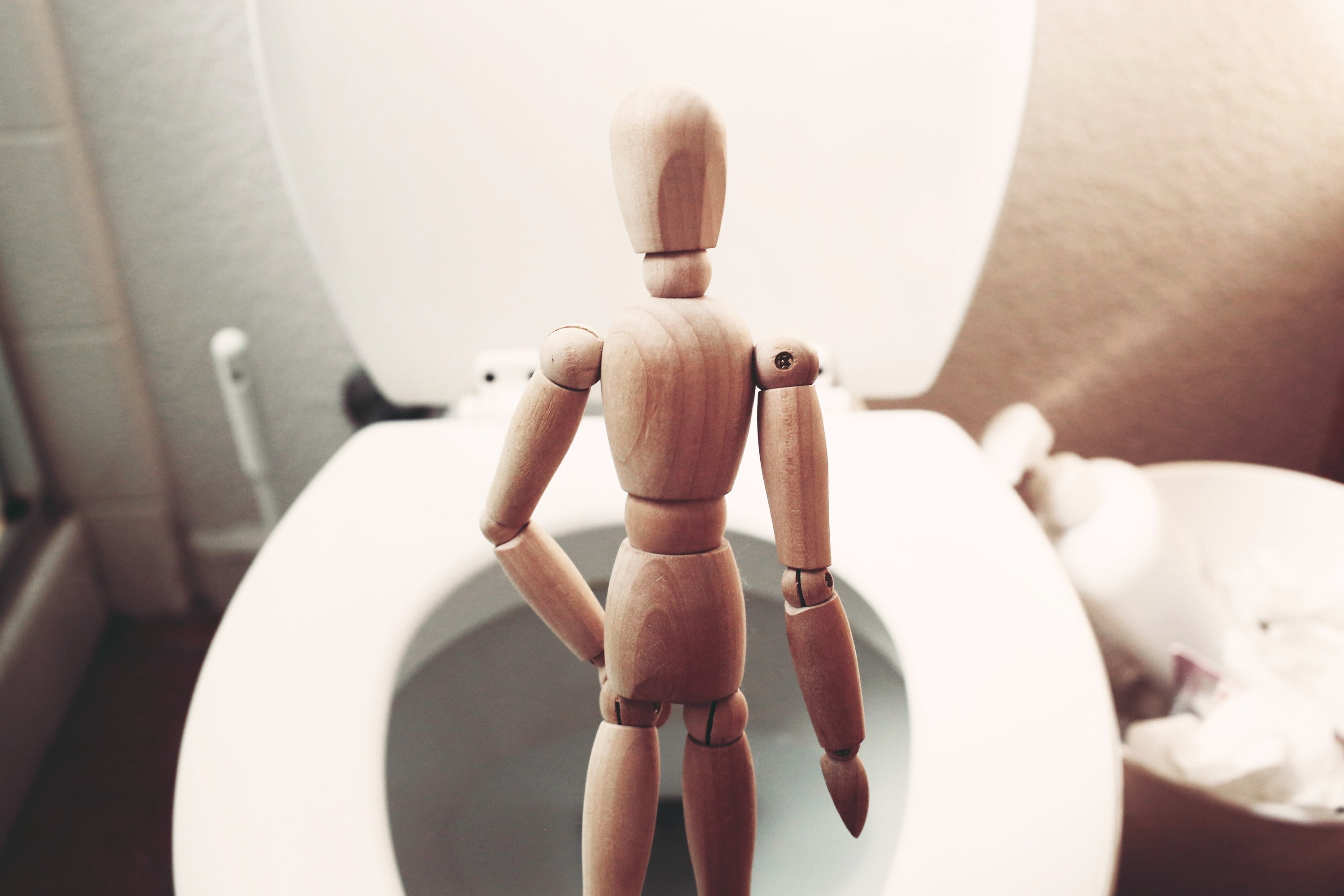 A wooden mannequin is seen standing over a toilet bowl