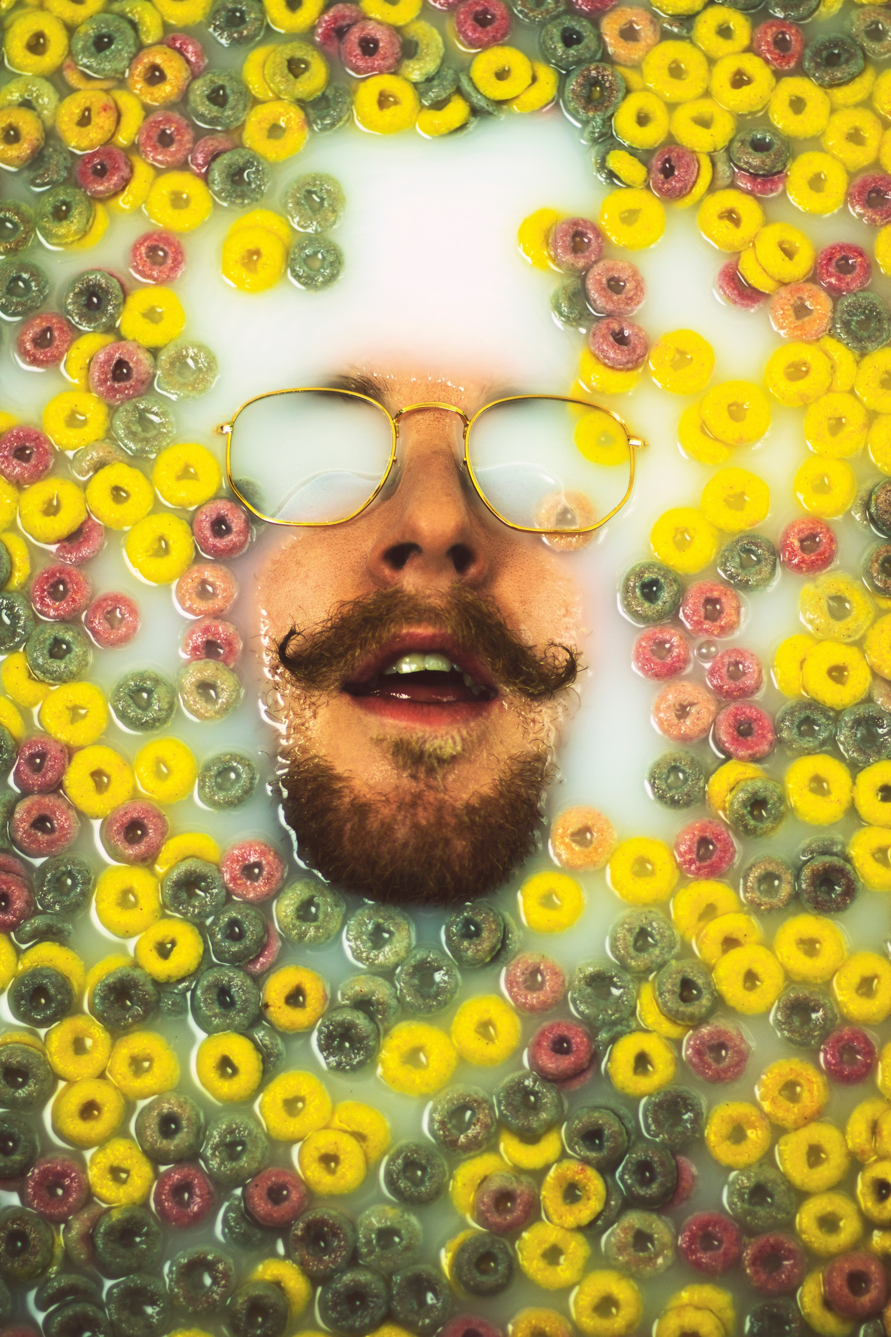 A man's face with a handlebar mustache and gold glasses is submerged in milk and fruit loops