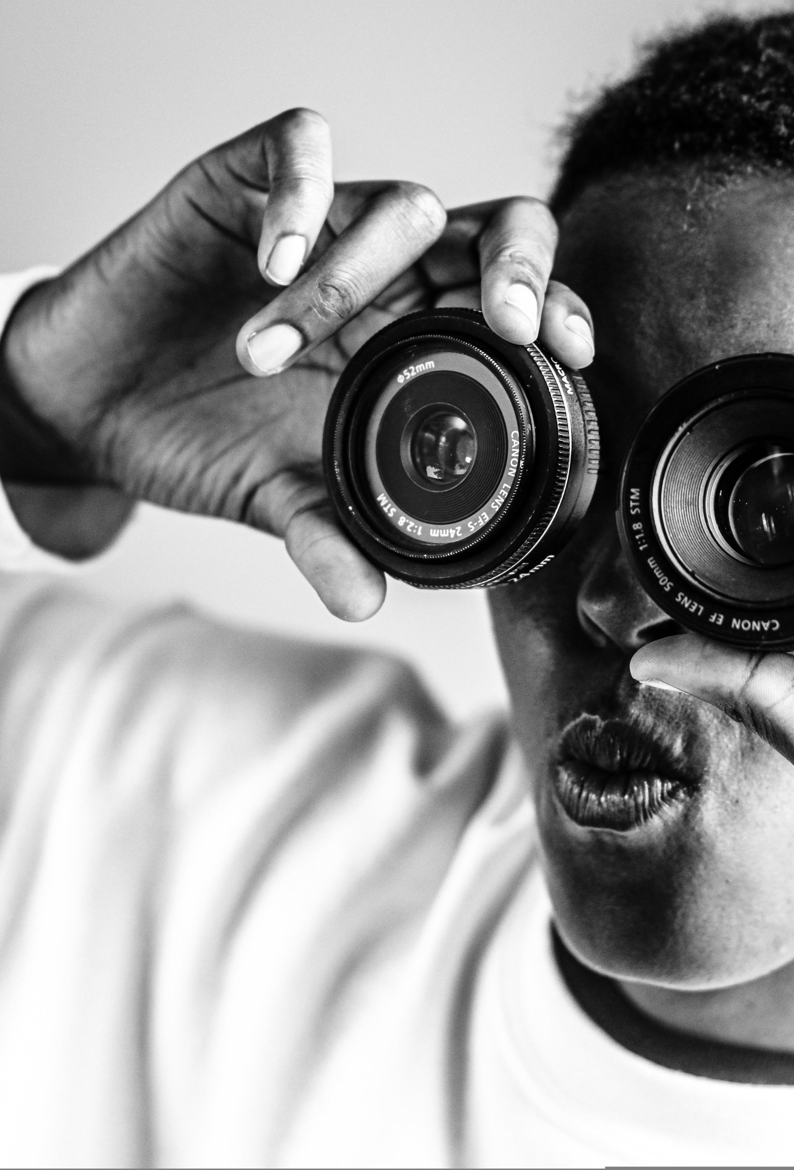 A man, depicted in black and white, is holding two camera lenses to both of his eyes