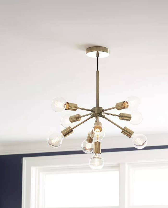 The brass light has 9 bulbs and arms in the shape of an asterisk