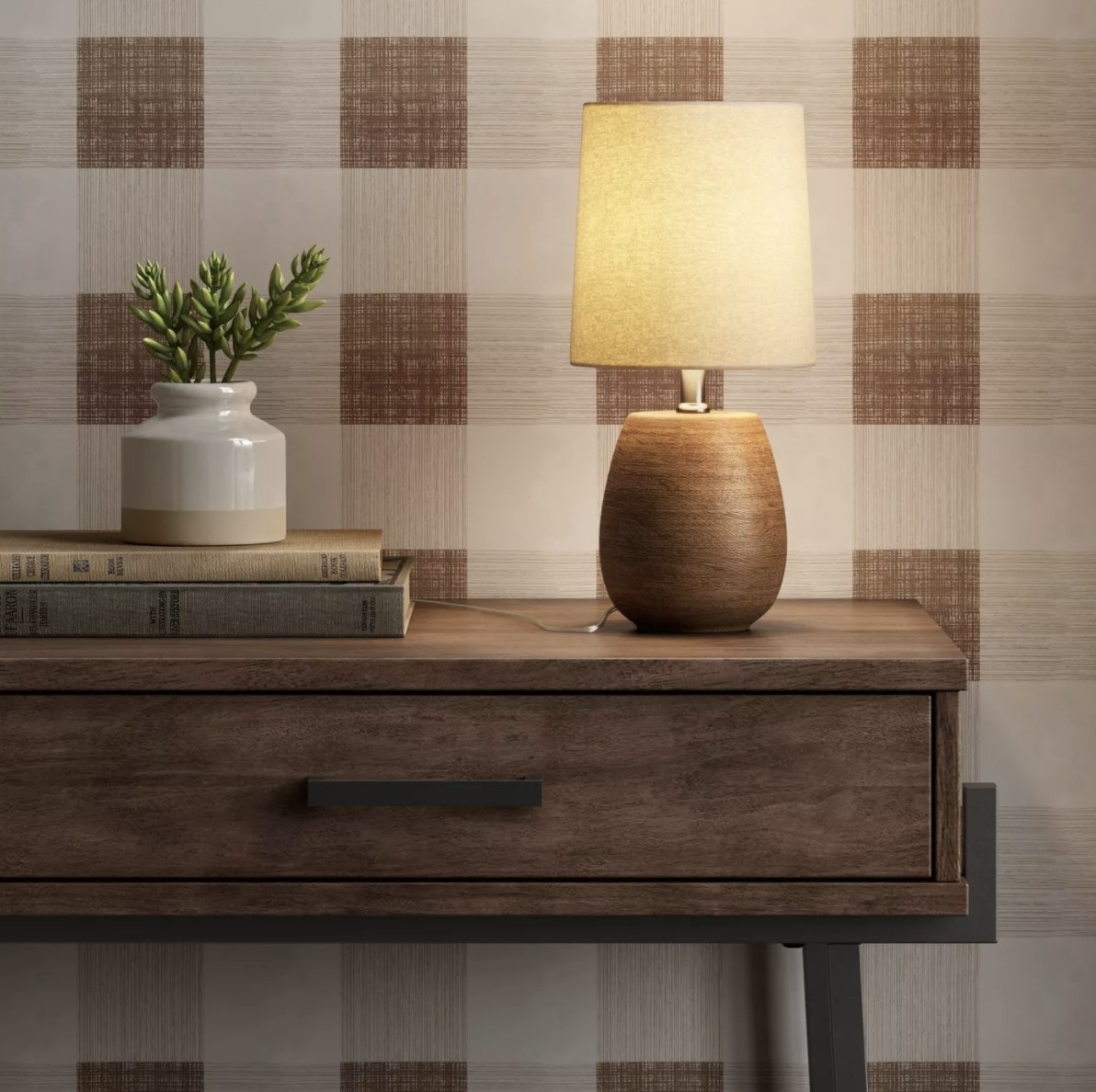 The brown wood lamp has a yellow glow and is on top of a table