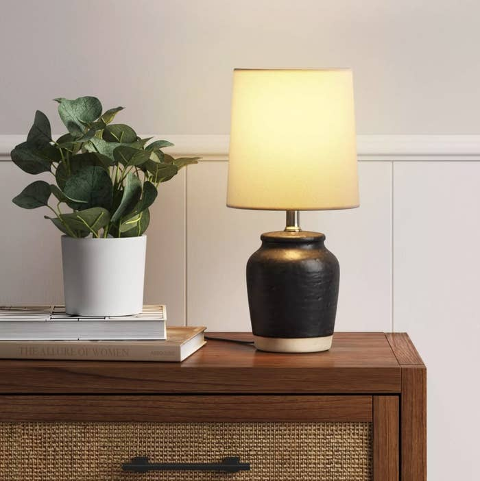 The black texture lamp has a light base and warm yellow light coming from the shade