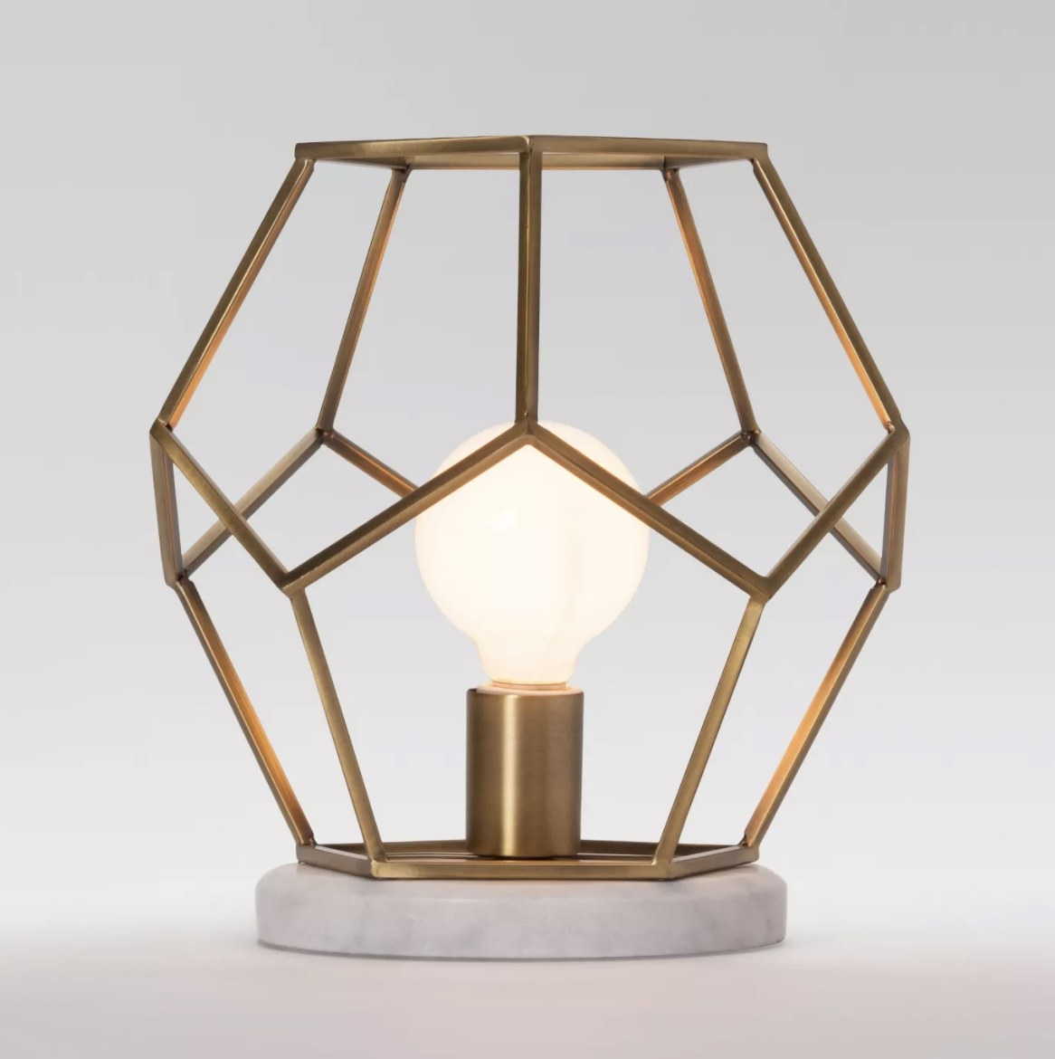 The lamp has a gold geometric outline frame and marble base
