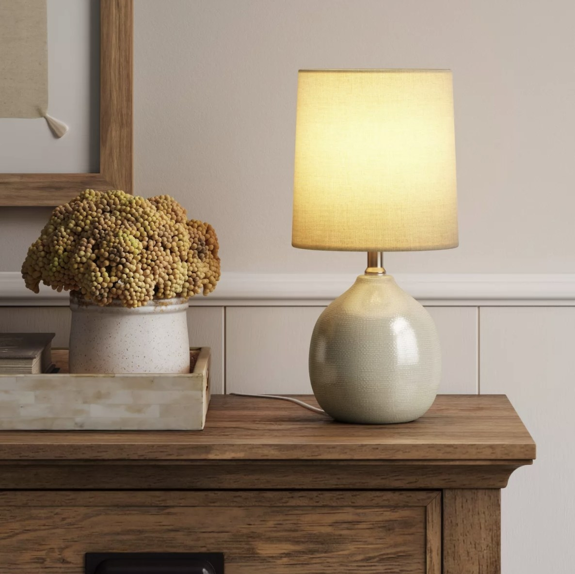 The ceramic lamp has a drum shade with a warm, yellow glow