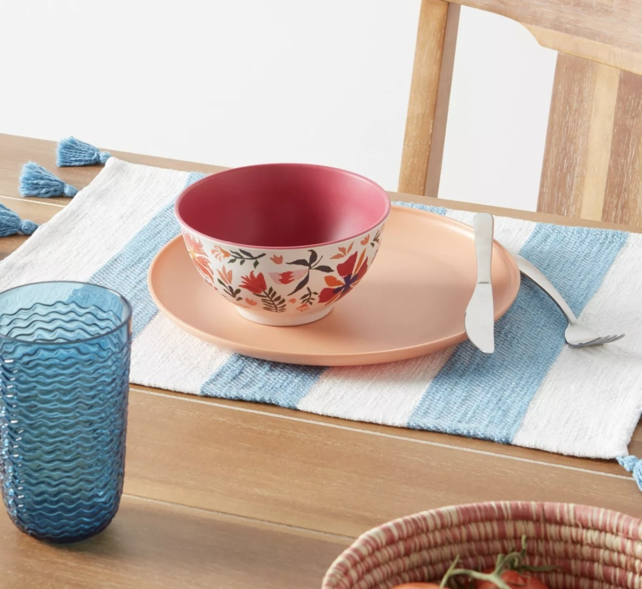 a place setting sitting on top of a blue and white striped placemat with tassles