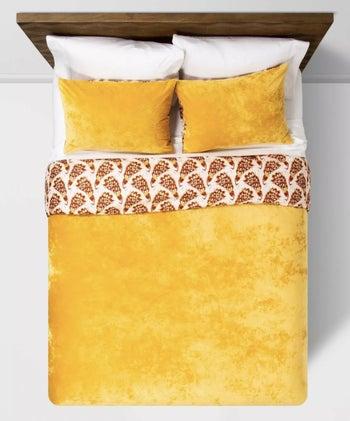 a mustard velvet duvet and sham set on a bed