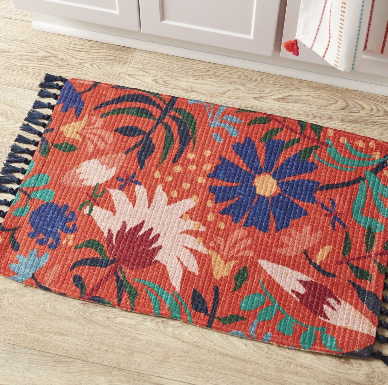 a floral braided rug with navy tassles