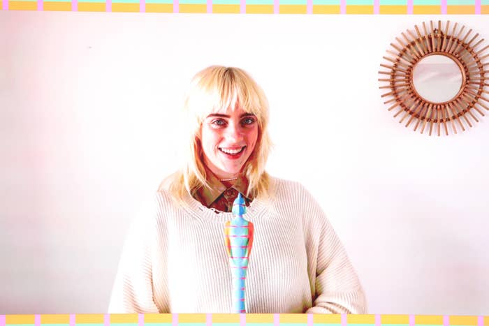 Billie smiling and wearing a thick sweater while holding her Brit award