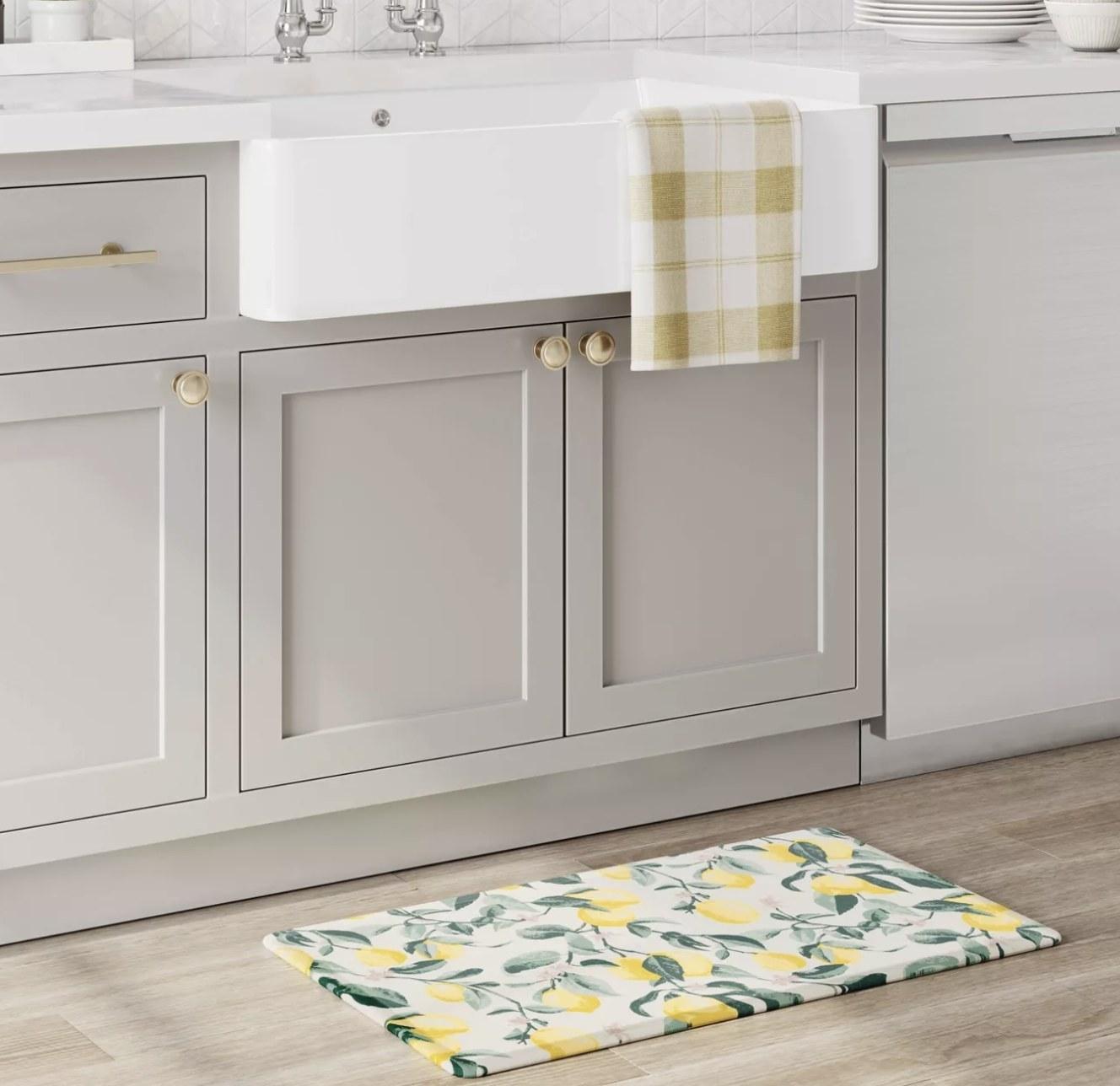 a lemon print bath mat under a sink