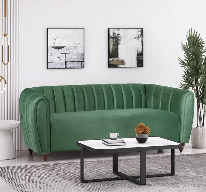a green velvet sofa in a living room