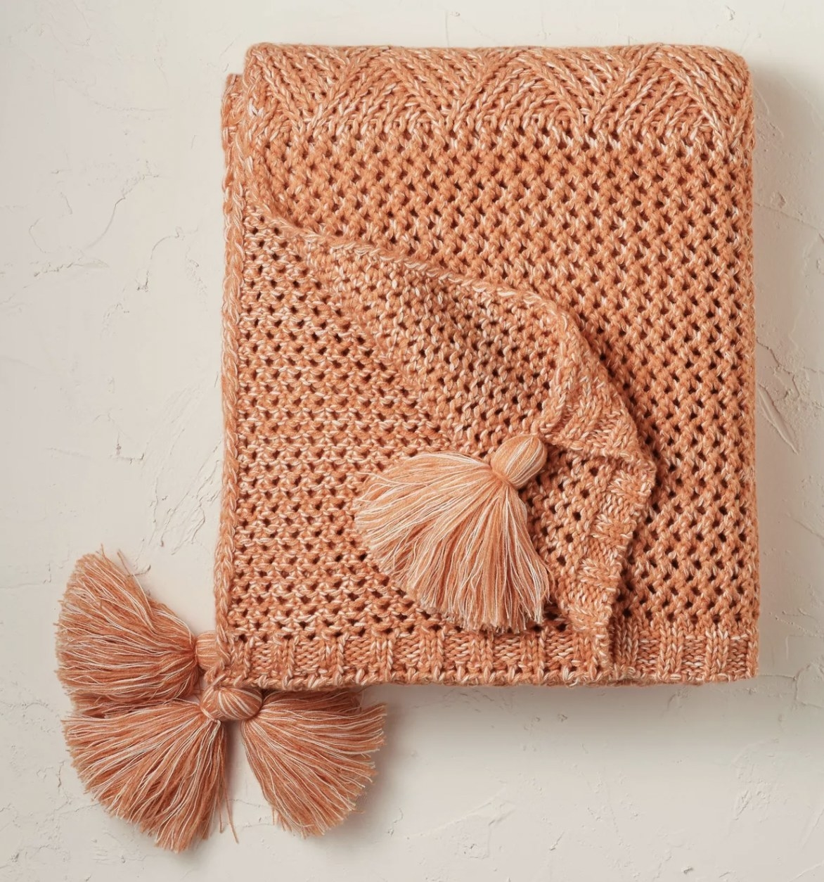a terracotta throw blanket with tassles