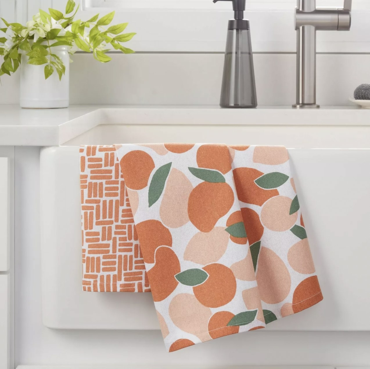 a kitchen towel set with oranges and abstract designs on them