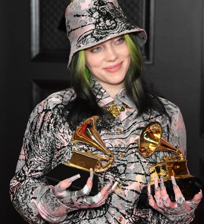 Billie holding two Grammys