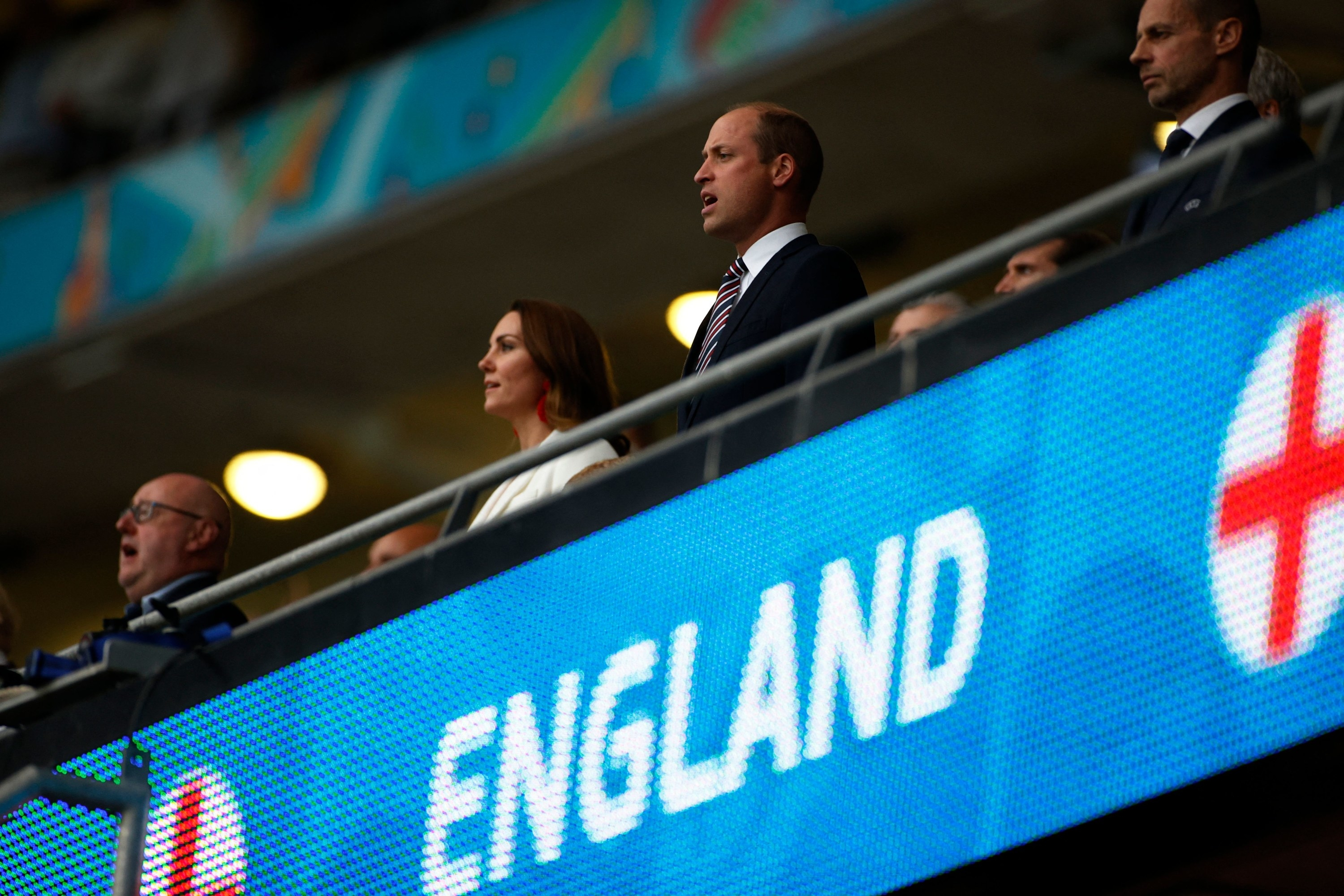 """Kate and William in the stands below an """"England"""" sign"""