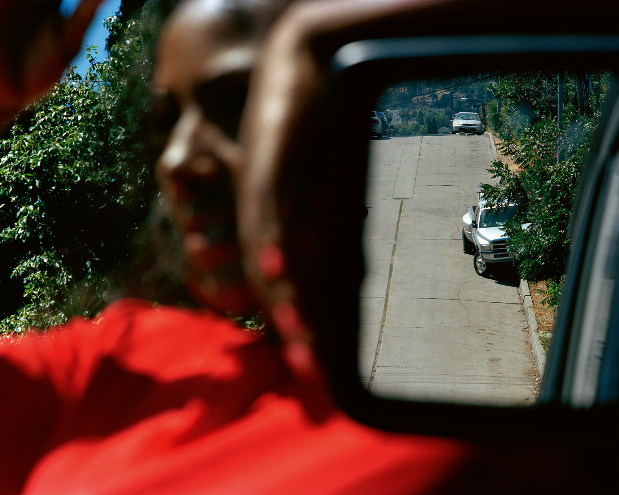 A photo where a woman is out of focus, but the road in the rearview mirror is in focus