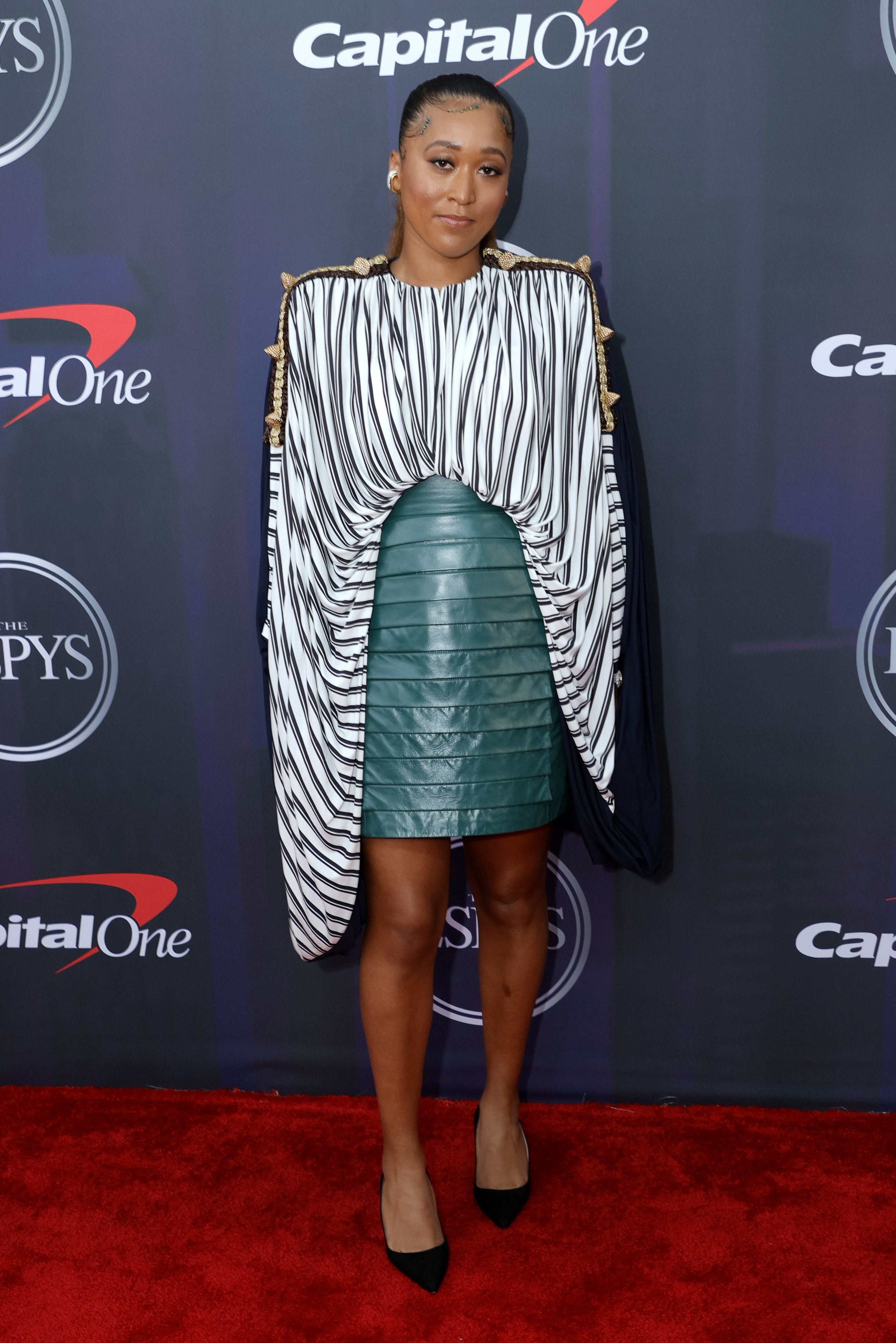 Naomi wore a striped blouse with oversized arms and a leather skirt