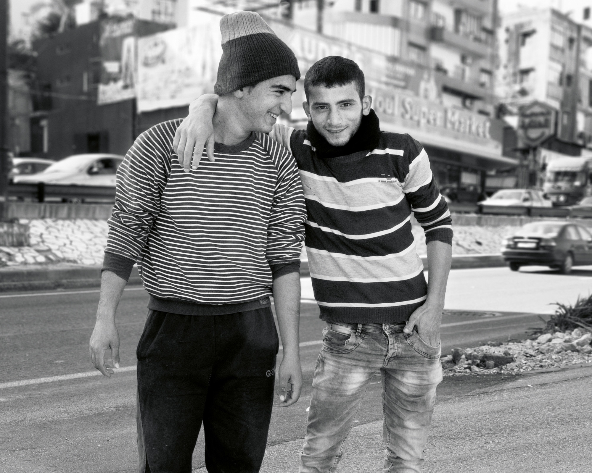 Two young men smile at each other and the photographer in Beirut