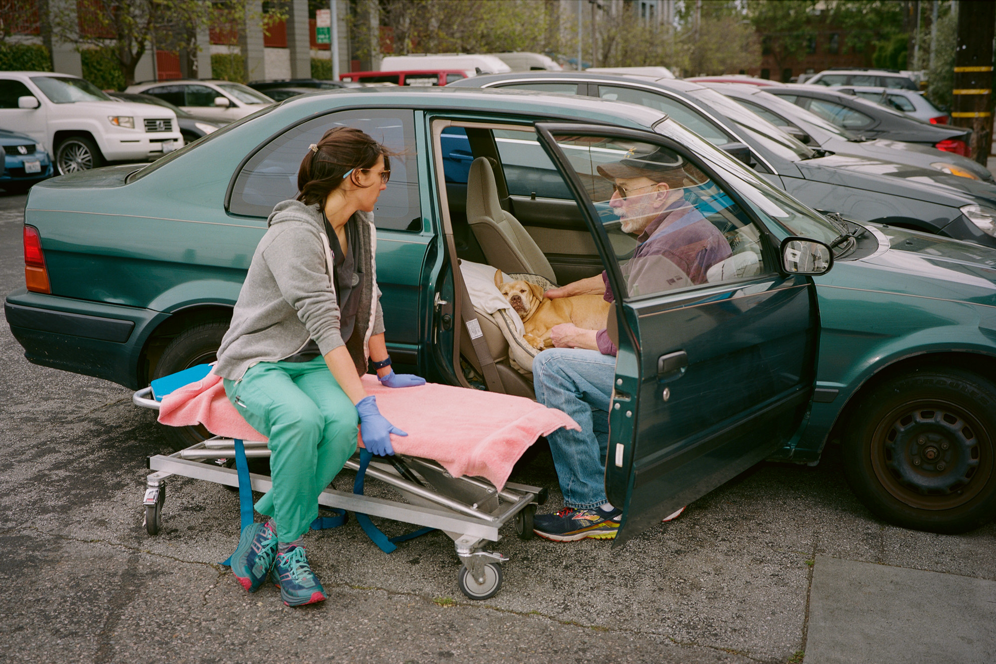 A veterinary nurse sits on a stretcher and talks to an older man who has his dog in the front seat of a car