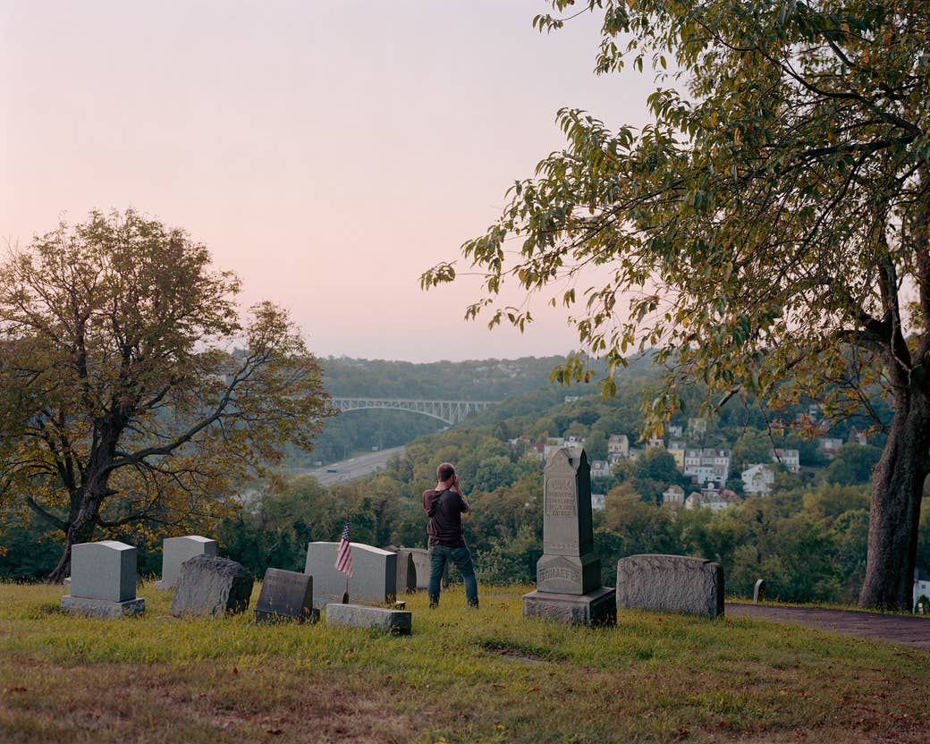 A man takes a picture in a graveyard, photographed from behind