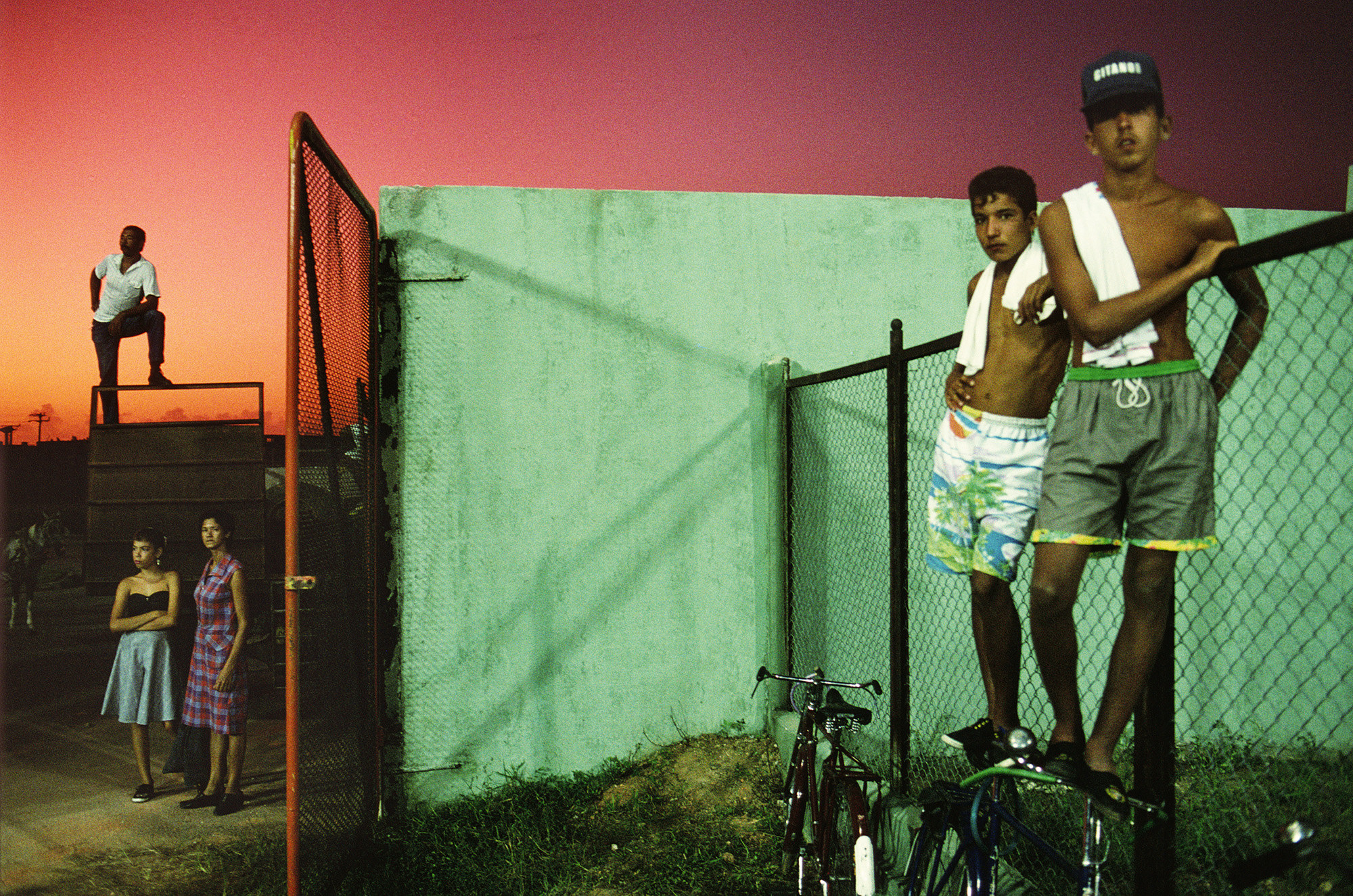 A man stands on a fence at left, two women stand below him, and on the right two young men stand on bikes by another fence