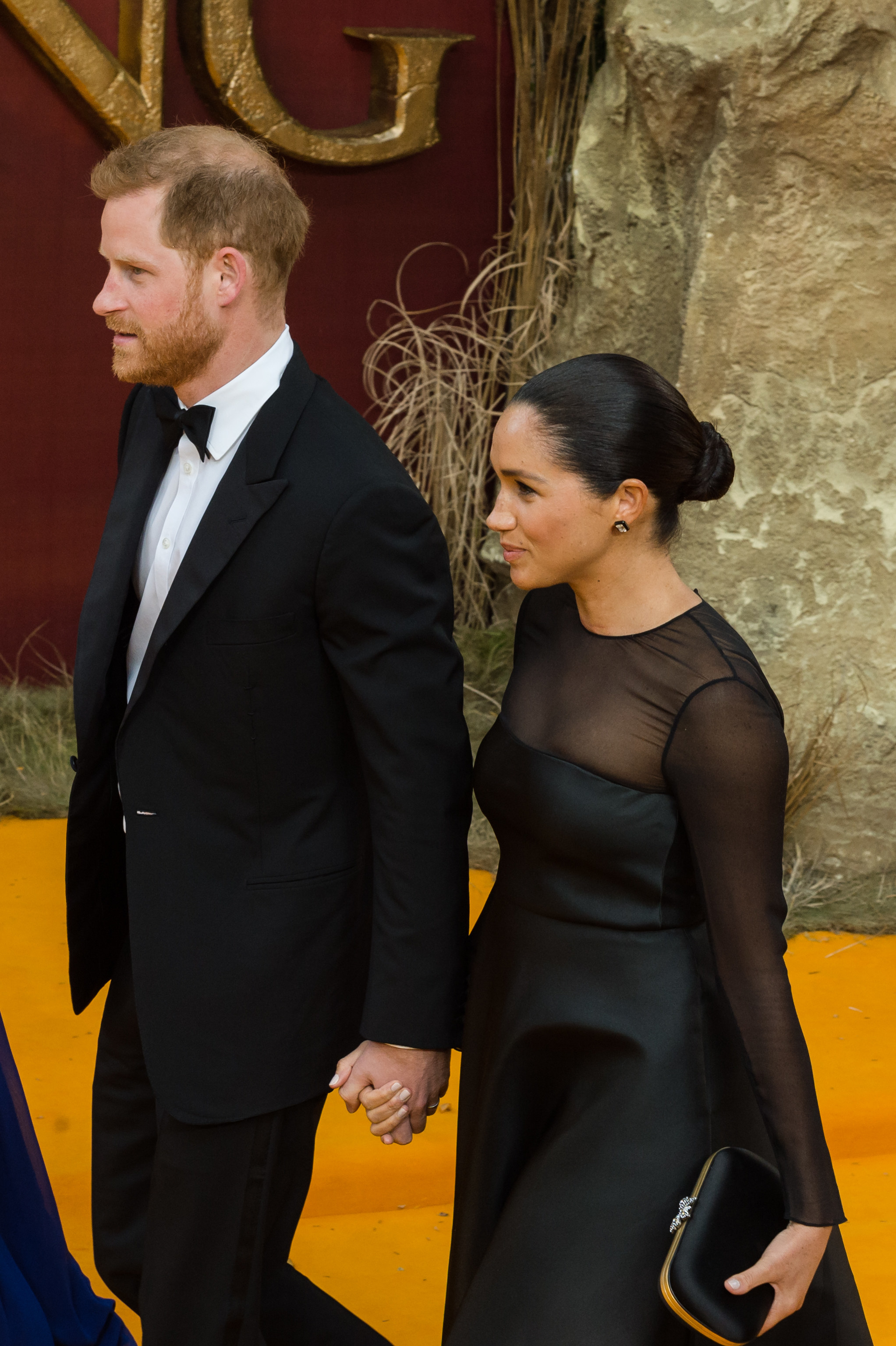 Prince Harry and Meghan walking hand in hand at an event