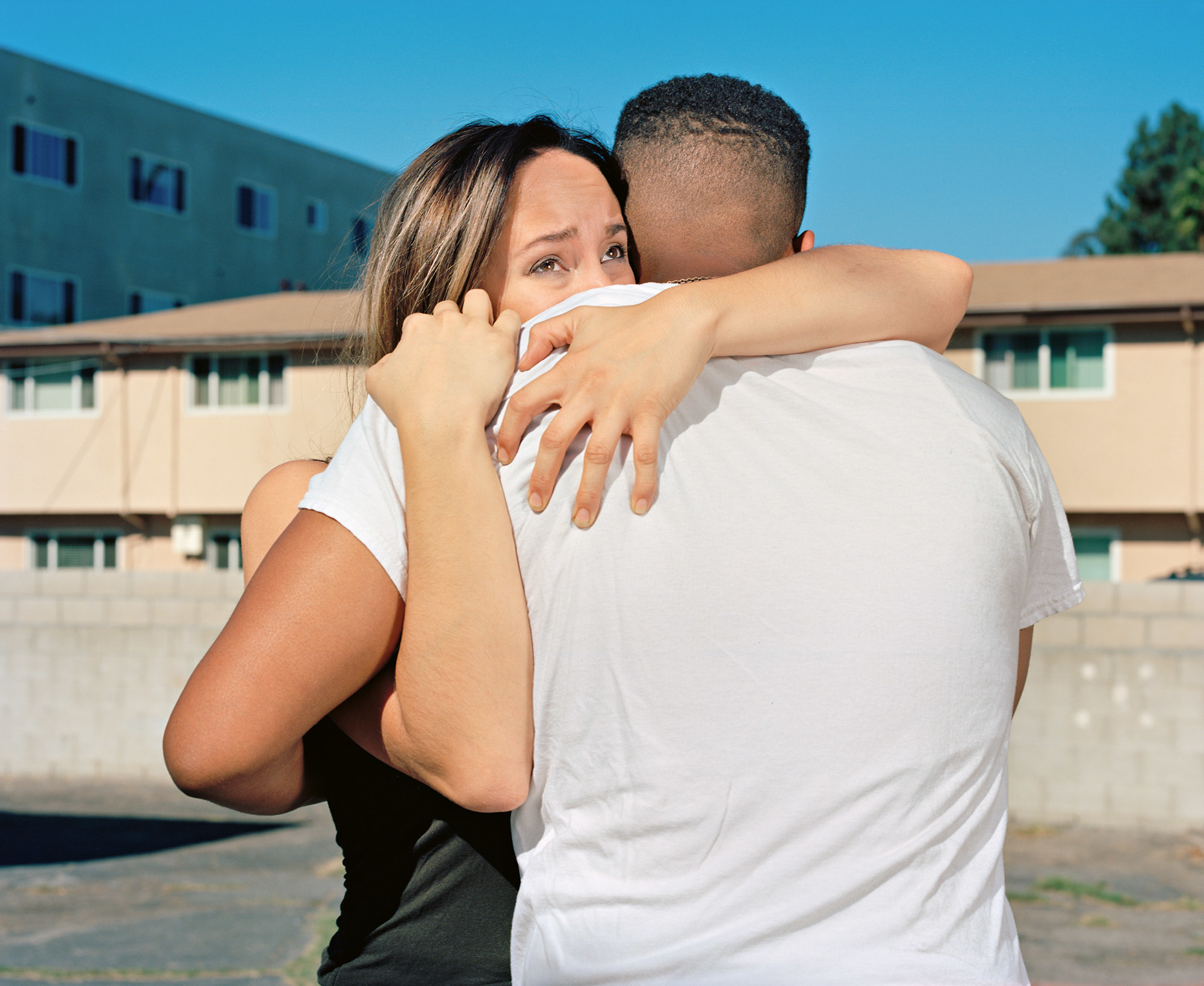A woman looks over a man's shoulder as she hugs him tightly in front of apartments