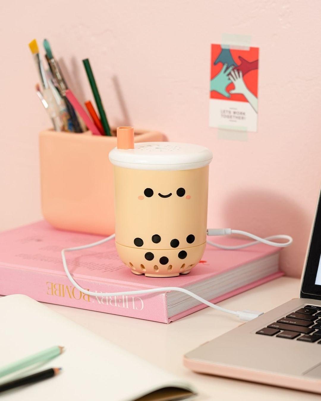 A mini air purifier on a desk; it's shaped like a boba tea