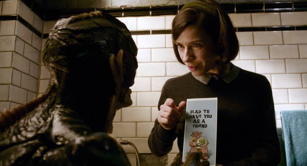 """Elisa talking to the creature with a card that says """"glad to have you as a friend"""""""