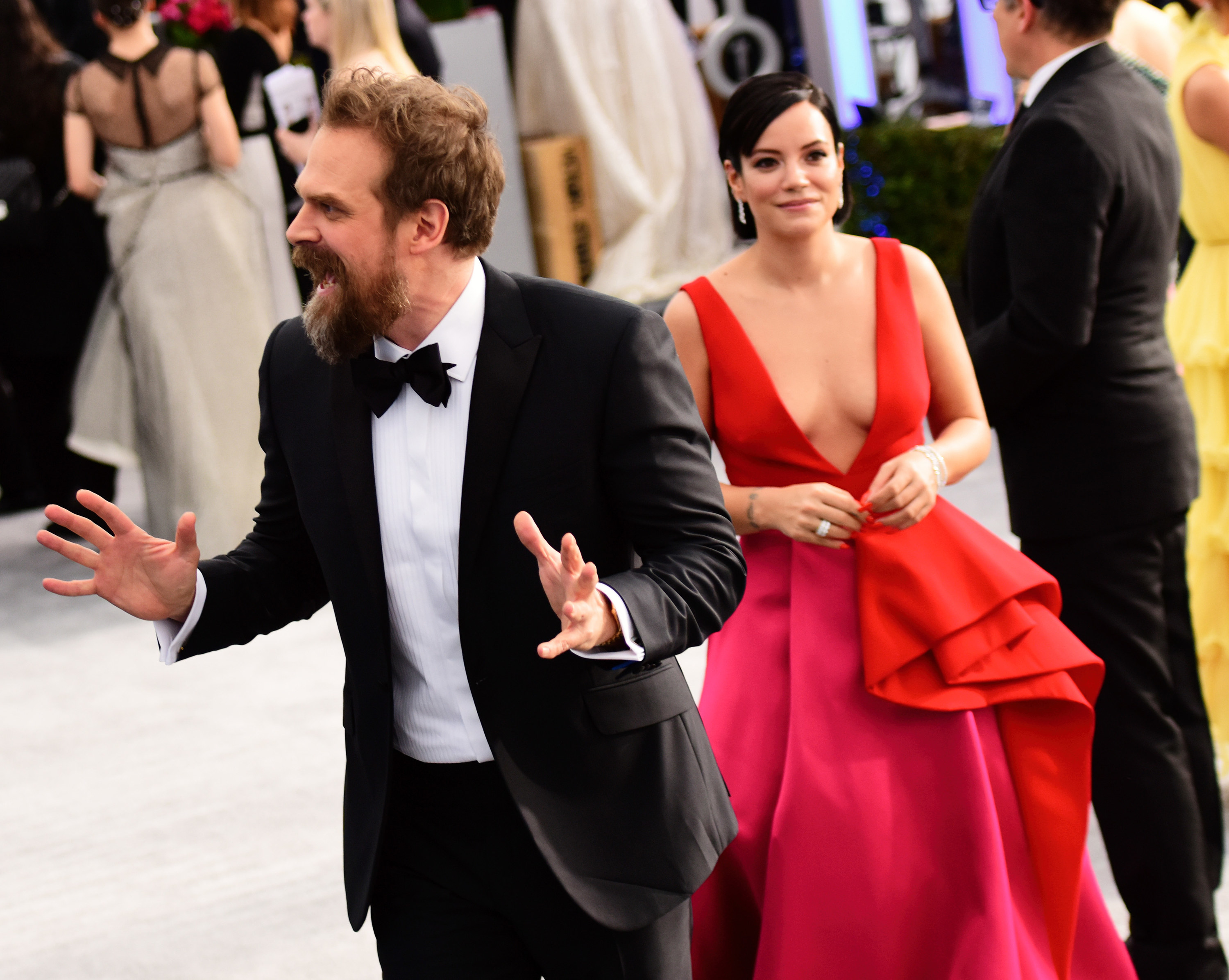 David Harbour making playful faces in a bow tie withLily Allen in a low-cut long dress