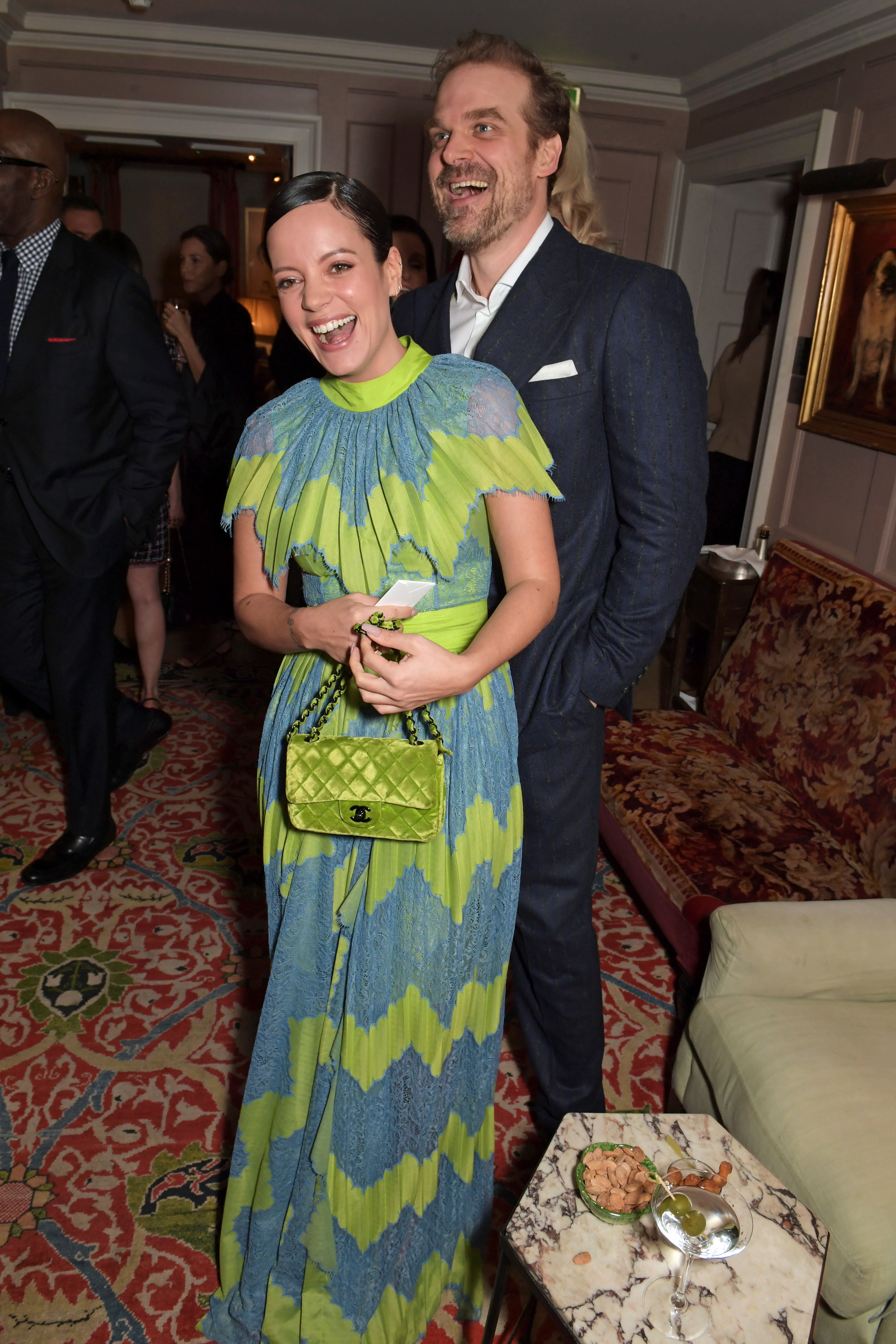 A smiling David Harbour standing behind a smiling Lily Allen