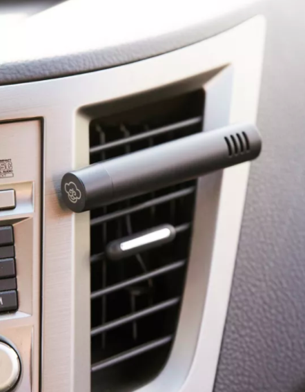 A tubular oil diffuser clipped onto a car vent