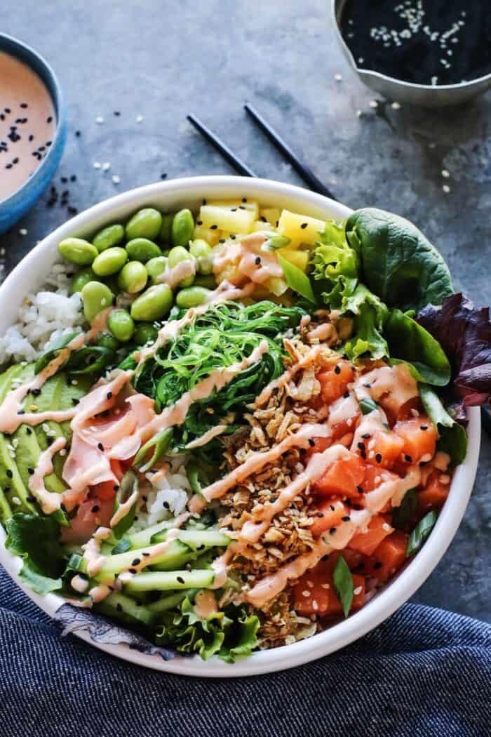 A poke bowl with tuna, cucumber, edamame, seaweed salad, avocado, and spicy mayo.