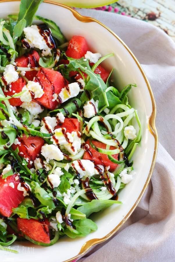 A salad with arugula, watermelon, and feta cheese.