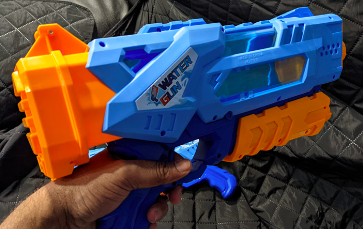 reviewer's hand holding the water gun