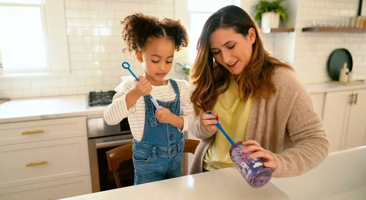 A parent and child cleaning a water bottle with the brushes