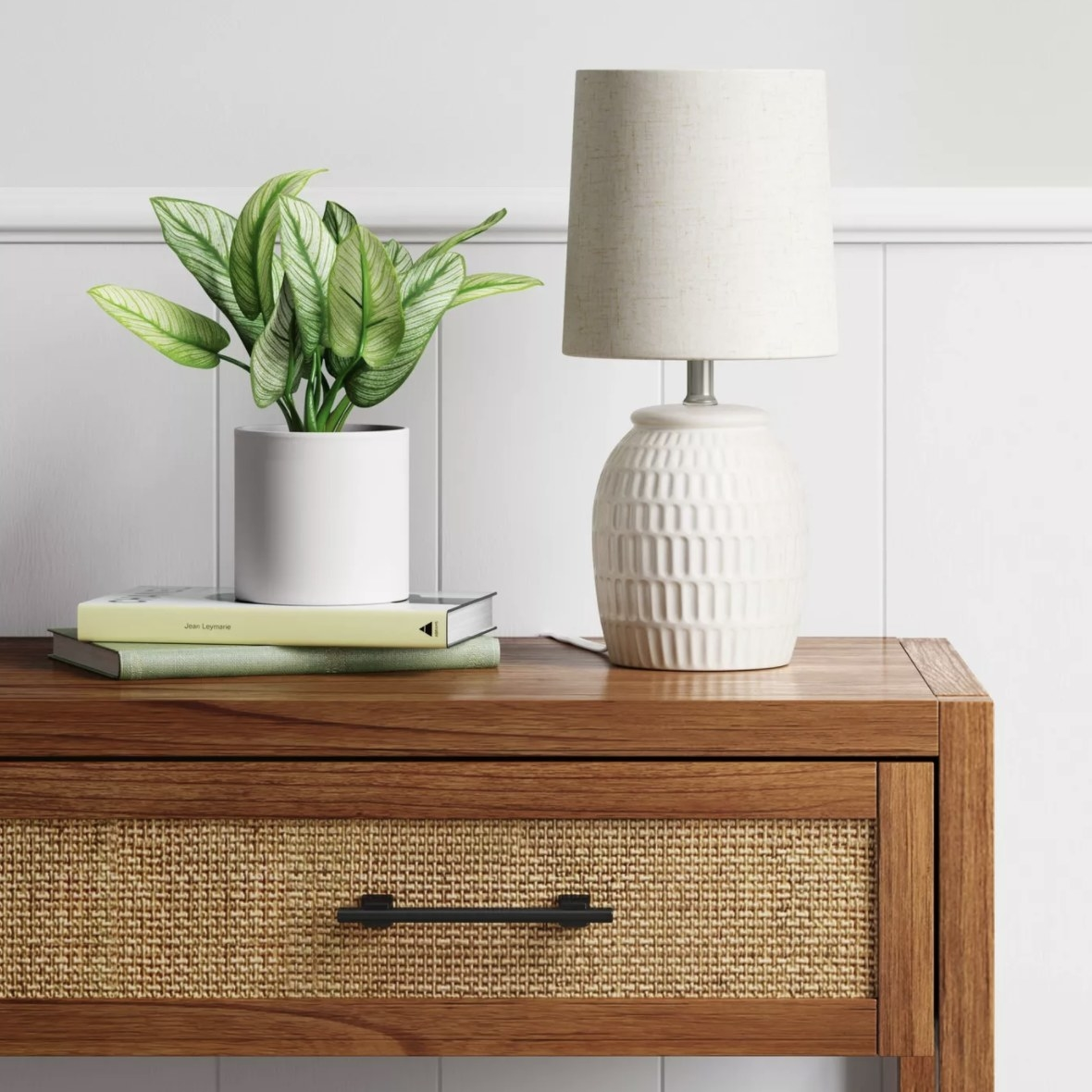 The white lamp has rectangular divets scooped out and has a linen-looking shade