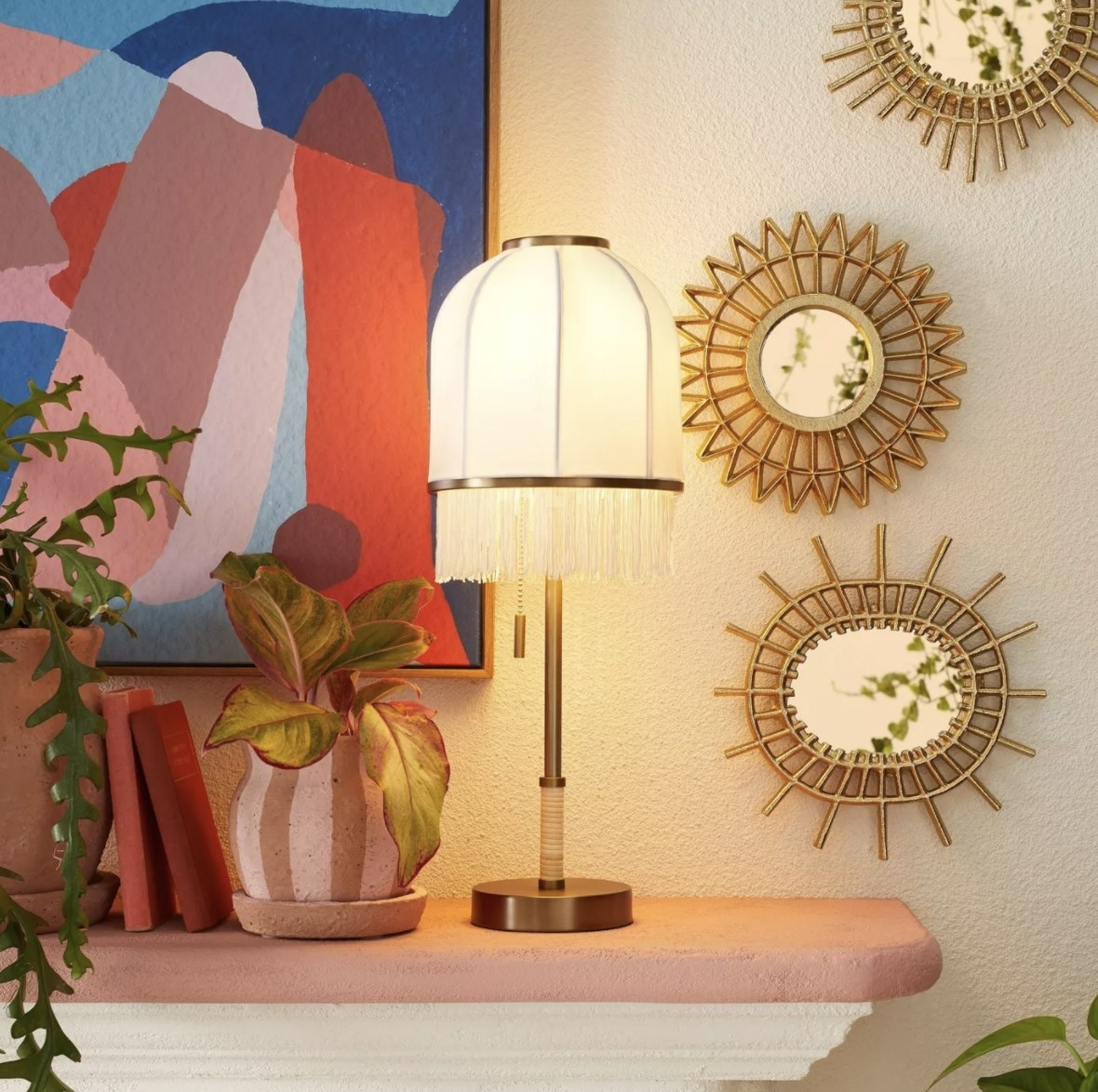 The cream lamp has a gold-tone base and fringe from the lampshade
