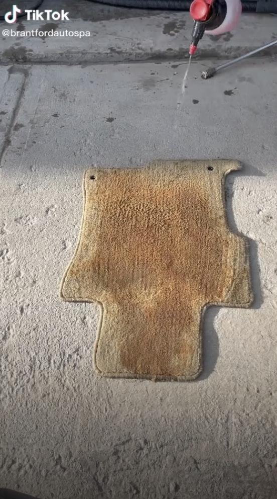 A brownish yellow car floor mat