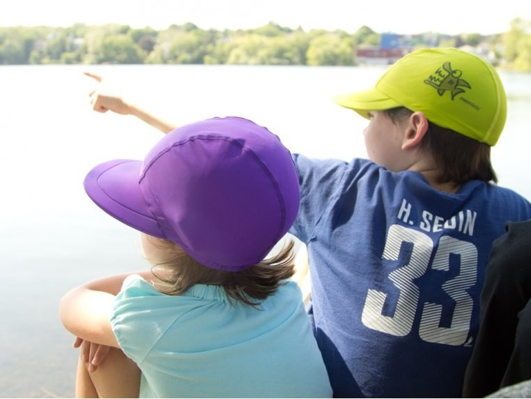 two kids wearing the swim lids while sitting near what looks like a lake