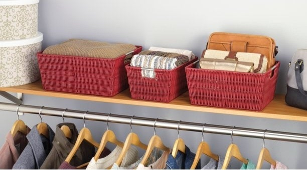 The bins in red holding items in a closet