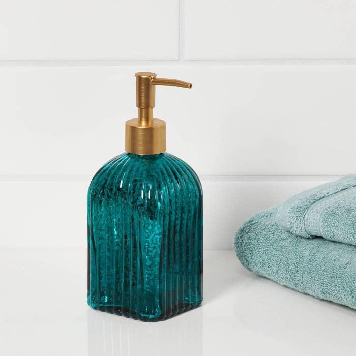 A teal glass soap dispenser