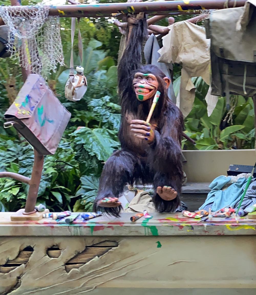 A chimpanzee swinging and using a paintbrush