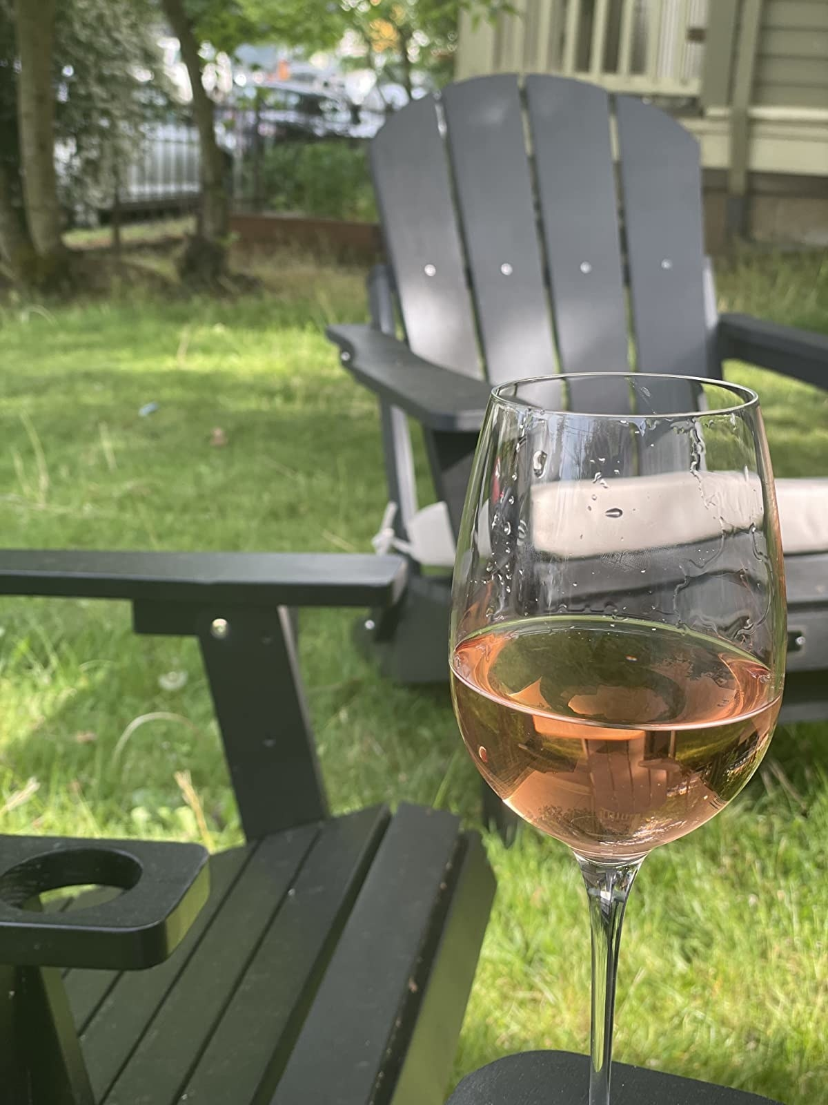 A wine glass with two Adirondack chairs in the background