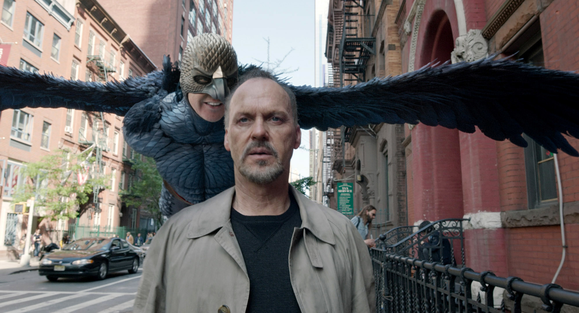 Michael Keaton on the street with his bird character behind him