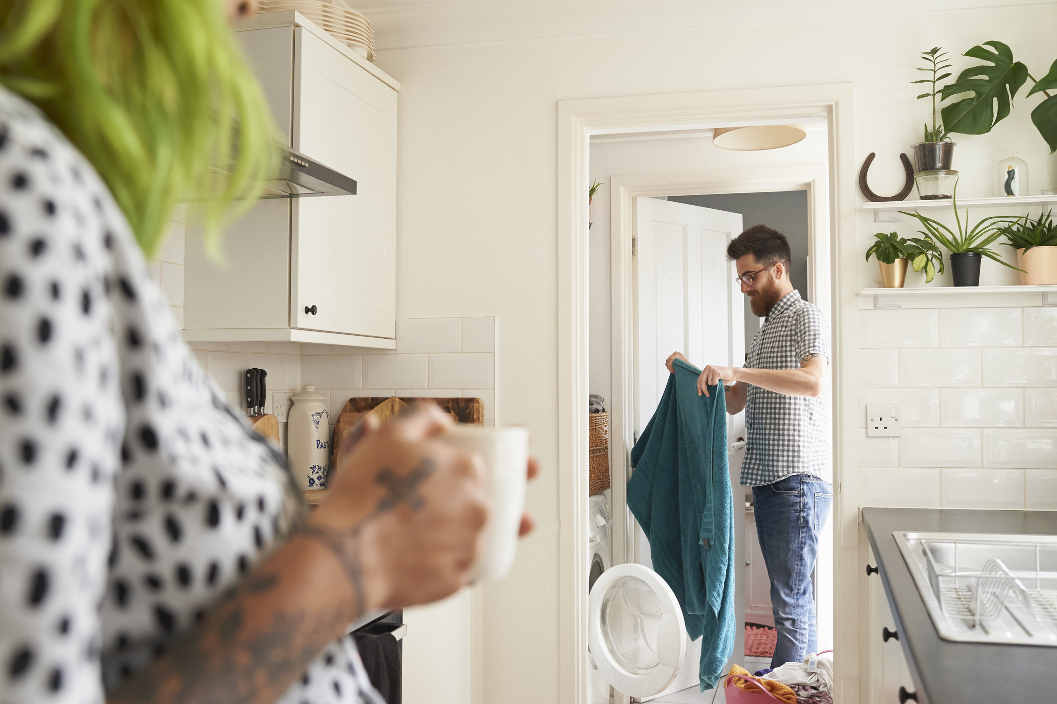Husband doing laundry while wife watches