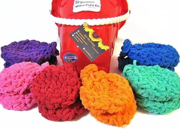 six crocheted water balloons and a red plastic bucket with a white handle