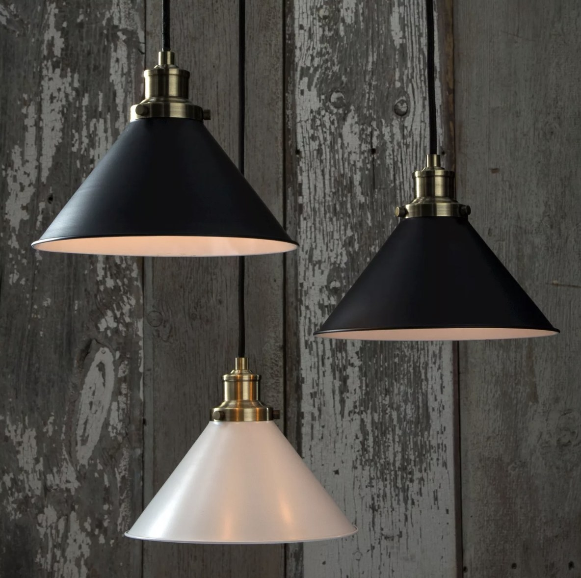There are three light fixtures — two black and one white — in the photo against a wooden background