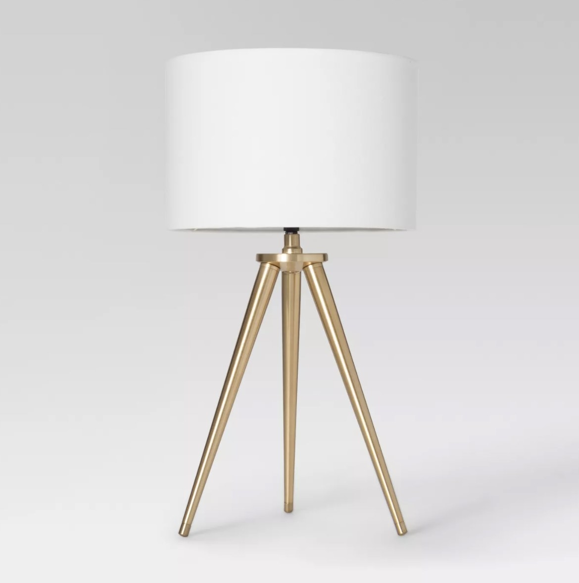 The gold-toned tripod base is sleek and classy with a white drum shade that sits right on top
