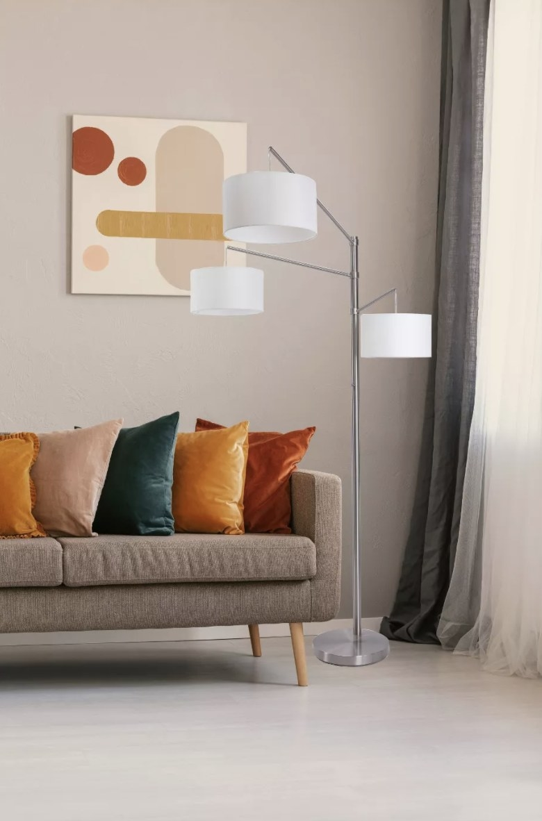 The brushed-nickel base has three stacked adjustable arms with linen shades and bulbs